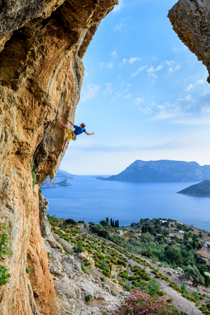 Scenic view, rock climber on a challenging cliff. Travel destination Kalymnos, Greece.