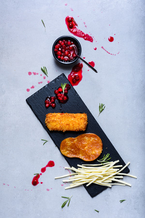 Cheese plates served with bread sticks and jam on a slate board. Top view. Фото со стока