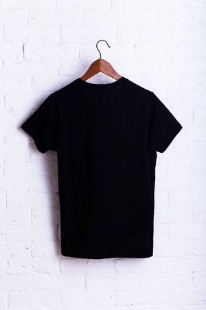 Black blank t-shirt, clothes hanging on a clothes hanger white brick wall background. Advertising discount mock up. Reklamní fotografie