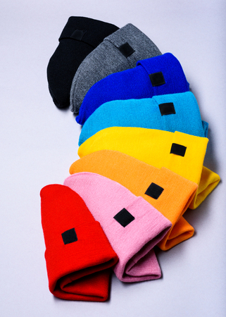 Knitted beanie hats. Colorful clothes items. Top view, copy space. Advertising discount mock up.