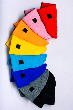 Knitted beanie hats. Colorful clothes items. Top view, copy space. Advertising discount space. Reklamní fotografie
