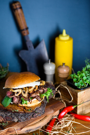 Home made hamburger with beef meat and mushrooms on wooden board. Close up. Reklamní fotografie