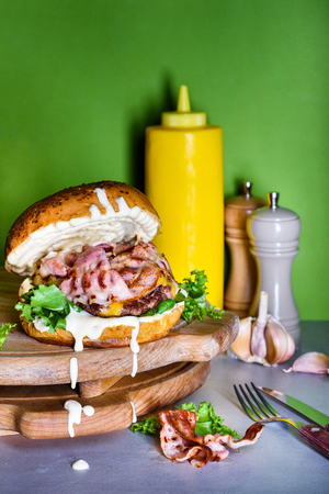 Burger with bacon, mayo and aioli. French fries snack. Hamburger fast food ingredients. Reklamní fotografie