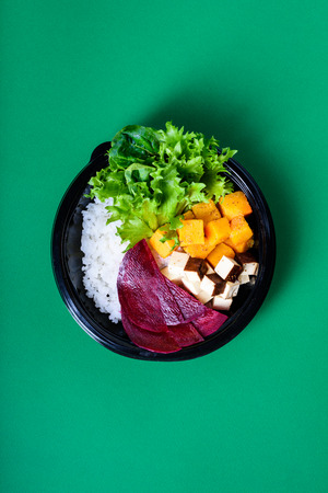 Hawaiian vegetarian poke bowl with tofu, chickpea, beetroot and pumpkin. Ready-to-eat, to go fast food. Healthy ingredients. Top view, flat lay.