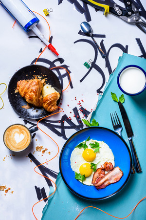 Traditional breakfast fried eggs with bacon, coffee and croissant, modern concept. View above.The Art of food.