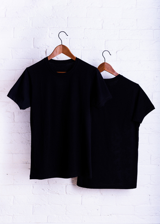 Black blank t-shirt, clothes hanging on a clothes hanger white brick wall background. Advertising discount mock up. Stock fotó