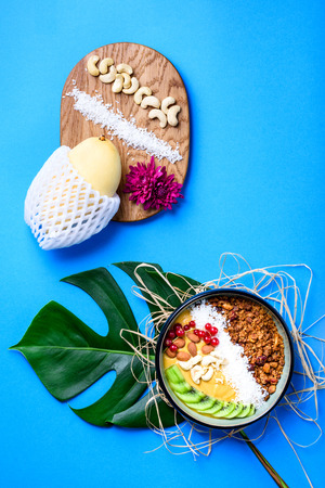 Smoothie bowl. Healthy breakfast. Fresh granola, muesli with coconut, fruits and nuts.  Flat lay, top view, close up. Reklamní fotografie