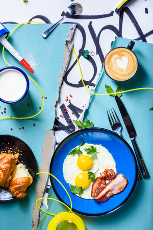Fried eggs and bacon breakfast, served with coffee and croissant. Sunny side up eggs hipster style. Top view.The Art of food.