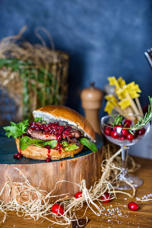 Tasty grilled beef burger with  lettuce and cranberry served on a rustic wooden table of counter, with copyspace. Reklamní fotografie