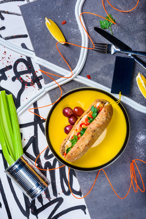 Gourmet grilled beef hot dog  loaded with toppings. Grey marble  background. Top view. Reklamní fotografie