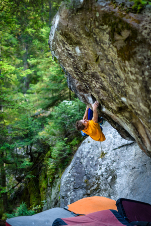 Strong climber on a challenging boulder problem. Magic wood, Switzerland. Travel destination, active lifestyle concept.