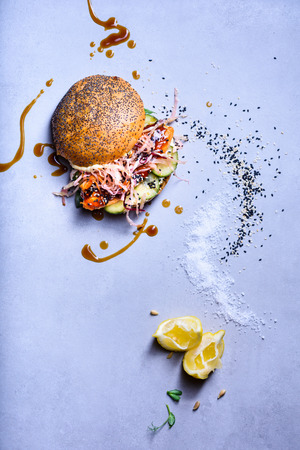 Salmon fish burger with with coleslaw and cucumber. Healthy diet concept. Top view, copy space. Reklamní fotografie