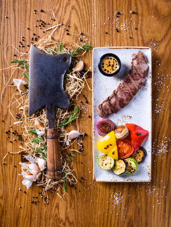 Barbecue rib eye Steak with a choper. Dry aged entrecote Steak with grilled vegetables. Top view, copy space. Foto de archivo