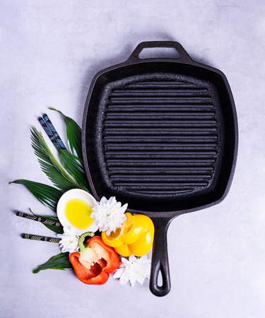Empty grill pan on a kitchen table with cooking ingredients. Flat lay background, copy space. Reklamní fotografie