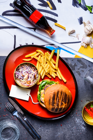Tasty grilled burger with beef, tomato, cheese, lettuce with french fries and coke drink. Top view with copy space Reklamní fotografie