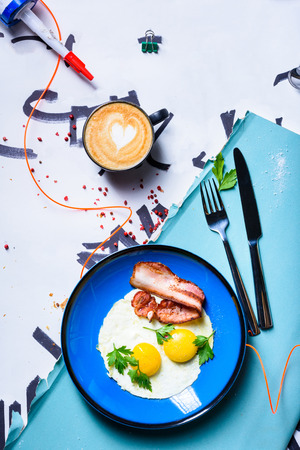 Fried eggs with bacon, english breakfast. Cup of coffee cappuccino. Top view, copy space. Reklamní fotografie