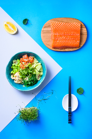 Hawaiian poke bowl with salmon, noodle and edamame. Asian trendy food sashimi. Top view, flat lay. Reklamní fotografie