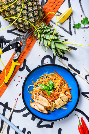 Stir fry noodles traditional Chinese wok, chopsticks, ingredients. Asian noodles with vegetables and chicken. Wok noodles. Copy space. Top view.