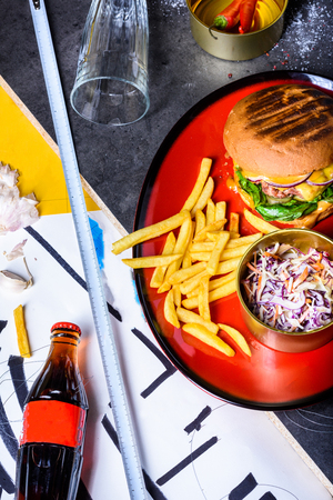 Tasty grilled beef burger with lettuce and mayonnaise served with french fries and pickled cabbage. Copy space, top view.