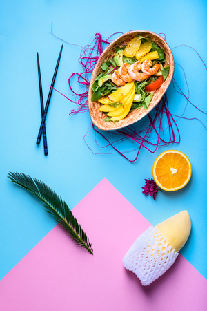 Hawaiian poke bowl with shrimps, noodle and mango. Asian trendy food sashimi. Top view, flat lay.