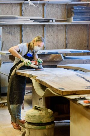 Inside the Wood Industry or Lumber Industry private sector, production of forest products. Female carpenter making slab furniture products, working in a mask and gloves at her workshop.