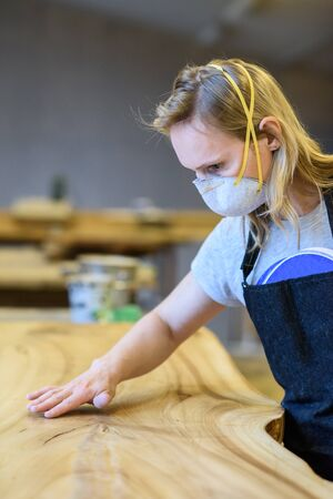 A woman in a work uniform working at the factory or workshop. The concept of women's equality and feminism. Female carpenter.