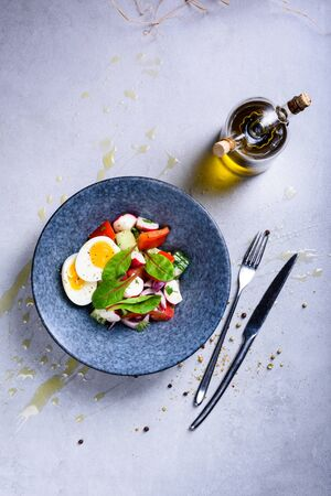 Fresh Spring vegetable salad with an egg. A bowl of healthy food ingredients. Vegan diet plate. Top view, grey backgroung.