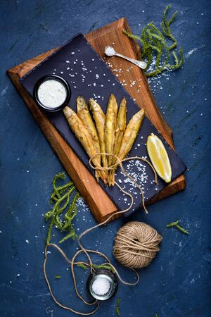 Fish and chip, traditional english seafood snack, tartar souce and lemon. Top view, copy space. Reklamní fotografie