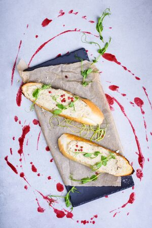 Chicken liver pate appetizer on crispy toast bread with cranberry sauce. Dinner party starter sandwich. Top view. Stock Photo