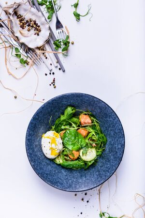 Green spring salad with spinach, salmon and egg in a bowl. Healthy eating concept.  Mediterranean recipe. Top view, copy space. Reklamní fotografie
