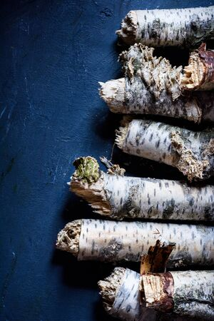 Birch firewood, logs stacked on the blue background, prepared for fireplace. Nordic style.View above, flat lay. Reklamní fotografie