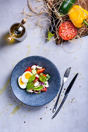 Bowl of Spring vegetable salad with an egg. Healthy cooking ingredients. Vegan diet plate. Top view, grey backgroung.