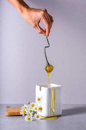 Honey, hand pouring sweet healthy  nectar in a white pot, Close up, cooking, bakery background. Reklamní fotografie