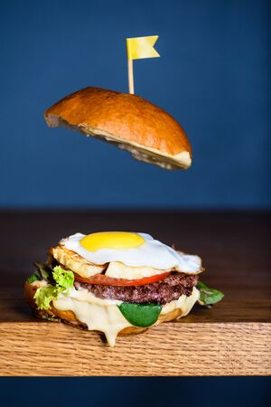 Delicious burger with beef, tomato, cheese, lettuce and egg on wooden counter. Copy space.