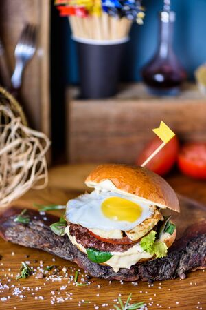 Grilled burger with beef, tomato, cheese, salad and egg on wooden counter. Copy space. Reklamní fotografie