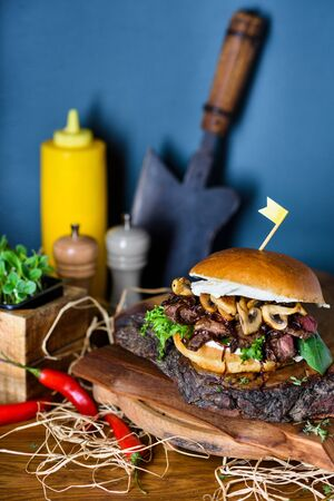 Beef steak burger medium well with mushrooms and cheese served on wooden board. Copy space. Reklamní fotografie