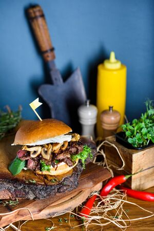 Grilled beef burger with mushrooms and cheese served on wooden board. Copy space.
