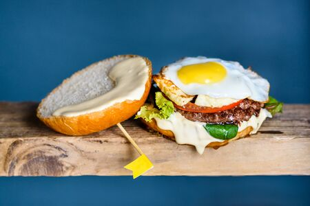 Burger with beef, tomato, cheese, salad and egg on wooden counter. Copy space.
