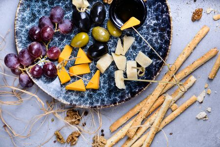 Cheese plate appetizer for party, cheese assortment platter with grapes, honey and nuts, flat lay. Grey concrete background. Reklamní fotografie