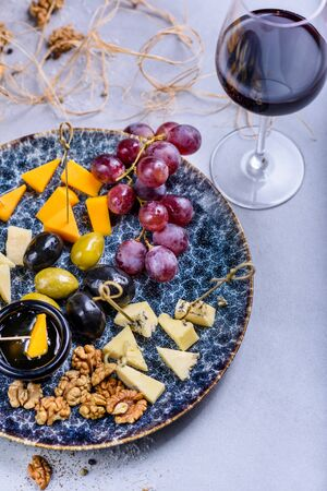 Cheese plate with grapes and olives. Snacks and cheese served with red wine. Top view, copy space. Reklamní fotografie
