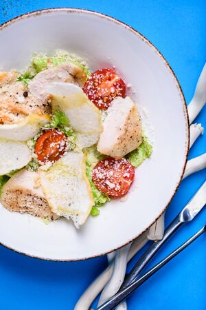 Caesar salad with chicken And cheese in a bowl. Salad with grilled chicken. Chicken breasts and fresh green salad leaves. Top view. Reklamní fotografie