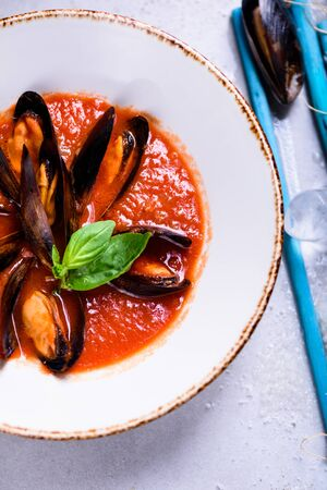 Delicious seafood mussels with tomato sauce and basil. Clams in the shells soup. Top view, copy space