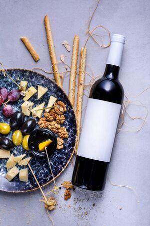 Cheese plate with grapes and olives. Snacks and cheese served with bottle of wine. Top view, copy space.