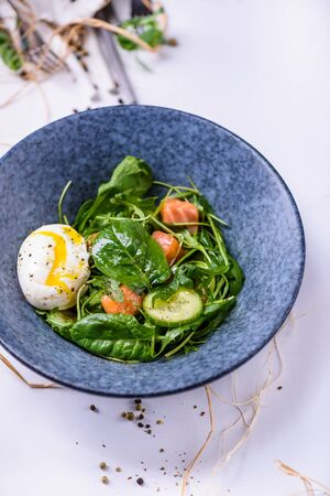 Salmon salad with spinach and poached egg in a bowl. Clean eating.  Mediterranean recipe. Top view, copy space.