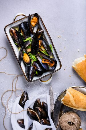 Mussels or clams, shellfish in a bowl on light background. Overhead view.
