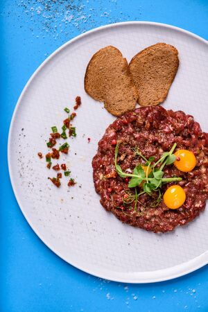 Steak Tartare, raw beef chopped and served with a quail eggs. Traditional Italian meat appetizer. Top view, blue background.