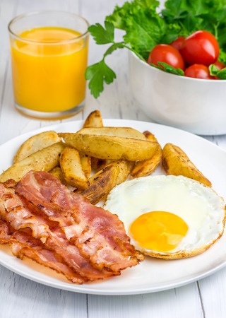 fat food: Hearty breakfast with bacon, fried egg, potato and glass of orange juice