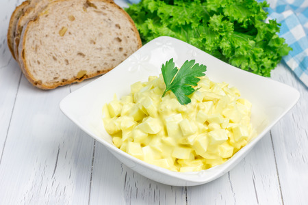 Egg salad in a bowl with bread and lettuce on background Archivio Fotografico