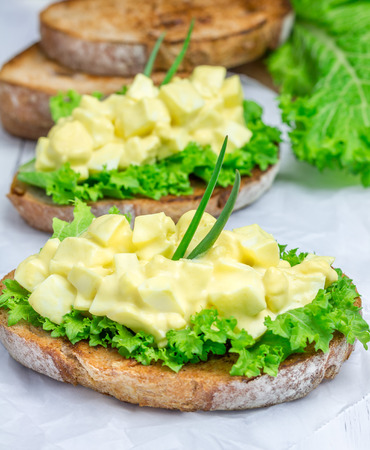 Egg salad and lettuce on nut bread garnished with green onion