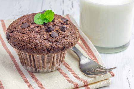 choco chips: Delicious chocolate muffin with choco chips and glass of milk closeup Stock Photo